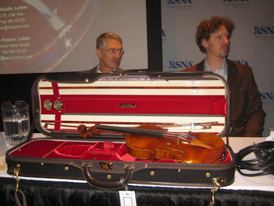 John Waddle, left, and Steve Rossow, sit behind their copy of the Betts Stradivarius.