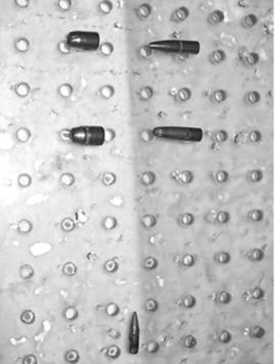 Experimental setup for evaluating MR-imaging related artifacts at 3-tesla includes five representative bullets placed on a plastic frame.