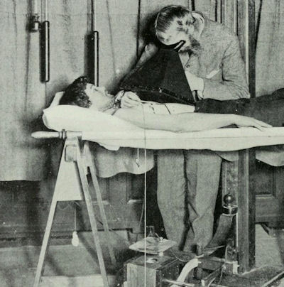 Physician drawing outlines on a patient's skin while looking through fluoroscope.